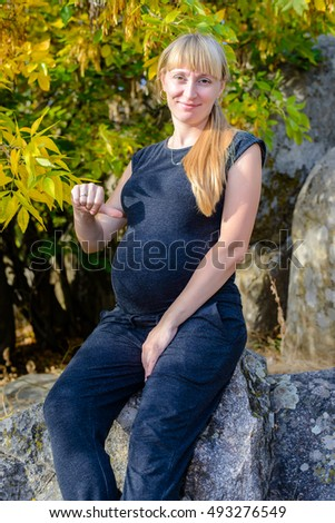 Active pregnant woman enjoying the fall foliage standing in front of a colorful yellow tree on rocks smiling at the camera