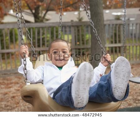 Active preschool hispanic boy on swing at school playground - stock photo