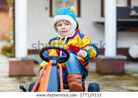 Active preschool kid boy having fun with toy race cars, outdoors. Child driving car. Outdoor games for children concept. - stock photo
