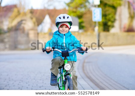 Active preschool kid boy in helmet biking on bicycle in the city. Happy child in colorful clothes and city traffic. Safety and protection for children.