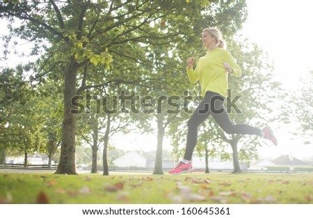Active pretty blonde jogging in a park on a sunny day - stock photo
