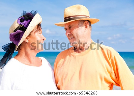 active Relaxed summer vacation senior couple of old man and woman standing on the beach - stock photo