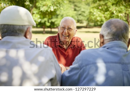 Active retired senior people, old friends and leisure, group of three elderly men having fun, laughing and talking in city park. Waist up - stock photo