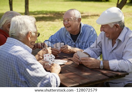 Active retirement, old people and seniors free time, group of four elderly men having fun and playing cards game at park. Waist up - stock photo