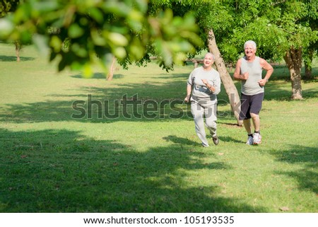 Active retirement, senior couple running and exercising in city park. Copy space - stock photo