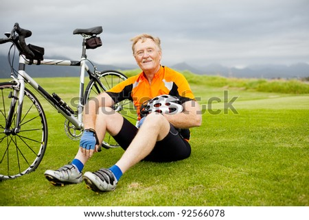 active senior bicyclist taking a break on the hill - stock photo