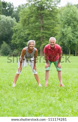 Active senior couple in the park doing gymnastics - stock photo