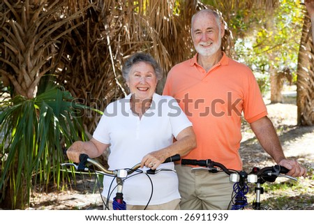 Active senior couple in the park with their bicycles. - stock photo