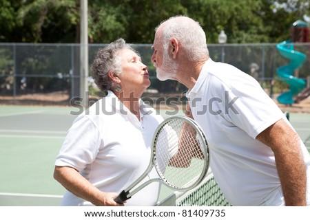 Active senior couple kissing on the tennis court. - stock photo