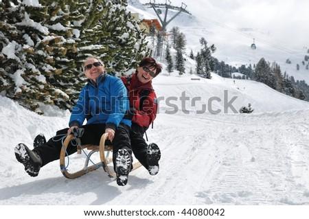 Active senior couple on sledge having fun in mountain snowy country - stock photo