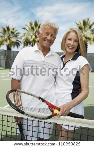 Active senior couple on the tennis court - stock photo