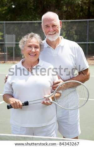 Active senior couple on the tennis courts. - stock photo