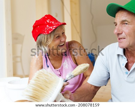 Active senior couple painting wall with brush in new house. They are having fun. - stock photo