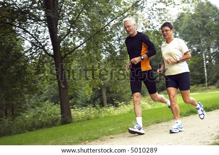 Active senior couple running in the woods. - stock photo