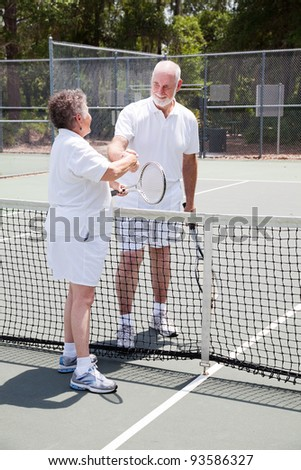 Active senior couple shakes hands over the tennis net. - stock photo
