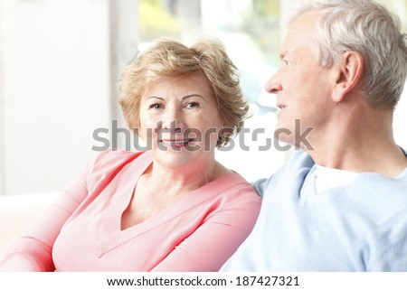 Active senior couple sitting at sofa in living room. - stock photo