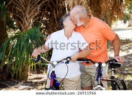 Active senior couple taking a break from cycling to kiss each other.