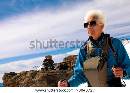 Active senior man hiker. Adventure trekking in the Swiss Alps. Concept: Active retirement. Copy space - stock photo