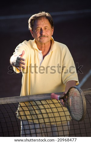 Active senior man in his 70s is offering his hand on the tennis court with tennis racket in other hand. Outdoor, sunlight.