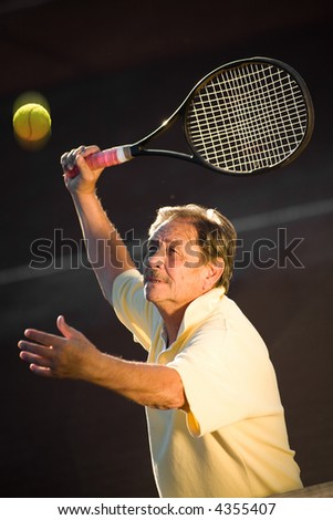 Active senior man in his 70s is playing tennis. - stock photo