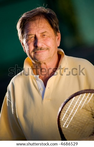 Active senior man in his 70s is posing on the tennis court with tennis racket in hand. Outdoor, sunlight.