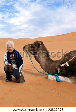 Active senior man on adventure camel trek in the Sahara Desert. Location: Erg Chebbi dunes in Morocco - stock photo