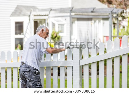 Active senior man painting a white picket fence - stock photo