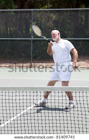 Active senior man playing a game of tennis. - stock photo