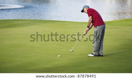 Active senior man putting out on golf course beside lake. - stock photo