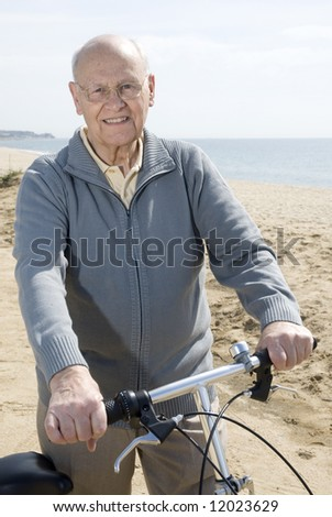 Active senior man riding his bike by the sea - stock photo