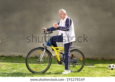 Active senior man sitting on bike and eating apple - stock photo
