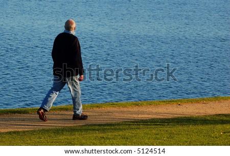 Active senior taking a brisk stroll round the lake - stock photo