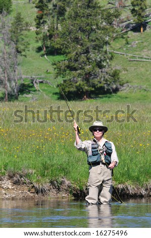 Active senior woman casting a fly-fishing rod in the Firehole River in Yellowstone Park. - stock photo