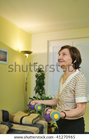 Active senior woman exercising at home with barbells - stock photo