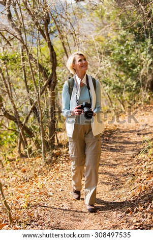 active senior woman hiking in forest with dslr camera  - stock photo