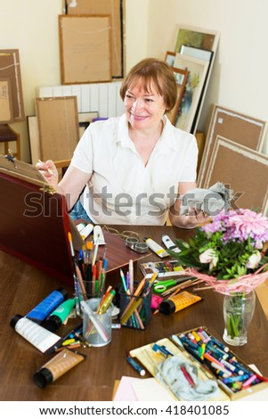 Active senior woman painting a new picture - stock photo