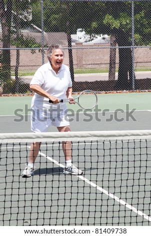 Active senior woman playing a game of tennis. - stock photo