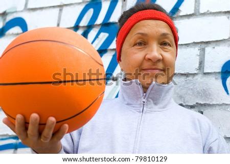 Active senior woman playing basketball - stock photo
