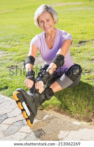 Active senior woman ready to go rollerblading on a sunny day - stock photo