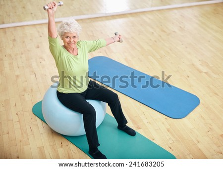 Active senior woman sitting on a pilates ball and lifting dumbbells looking at camera. Old caucasian woman exercising with weights at gym. - stock photo