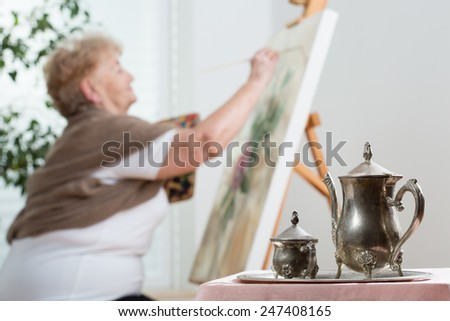 Active senior woman using easel during painting - stock photo