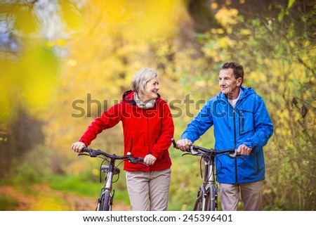 Active seniors having walk with bike in autumn nature. They having romantic time outdoor. - stock photo