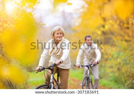 Active seniors riding bikes in autumn nature. They having romantic time outdoor. - stock photo