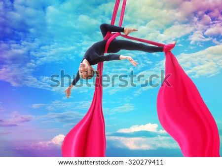 Active smiling sportive cheerful child training dancing performing on aerial silks or ribbons, hanging upside down in the blue rainbow sky Childhood, sports, happiness, active lifestyle concept. - stock photo