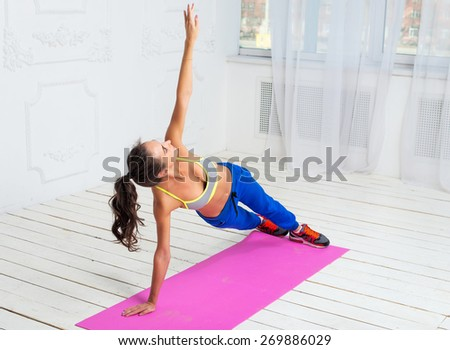 Active sportive woman doing handstand exercise practicing the side plank pose during yoga class in a gym - stock photo