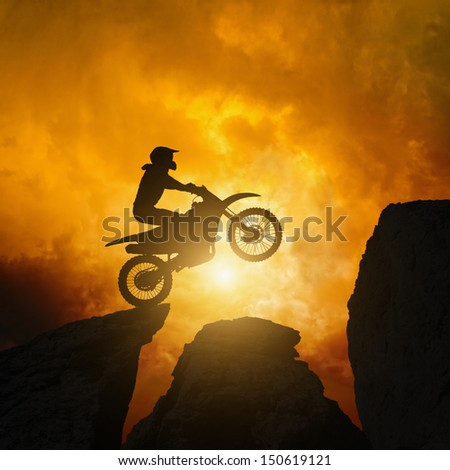 Active sports background - motorcycle rider silhouette, dramatic dark sunset in rocks