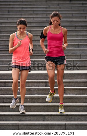 active sporty asian chinese women working out running down stairs outdoors for morning workout - stock photo