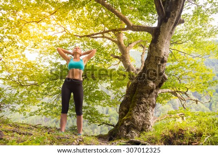 Active sporty girl raising arms, feeling  relaxed and free in beautiful natural environment. . Concept of natural, active, healthy, lifestile. - stock photo