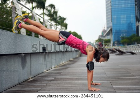 active strong woman doing pushup strengthening workout along outdoor city sidewalk with elevated legs - stock photo