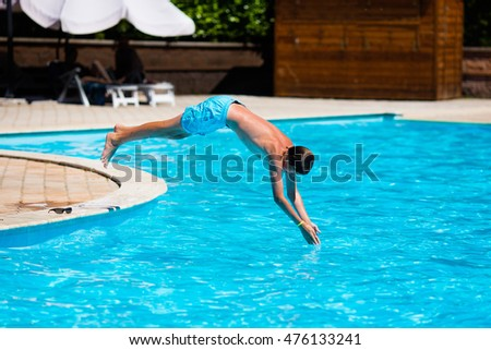 Active teenager boy jumping into an outdoor pool from spring board learning to dive during sport class on a hot summer day